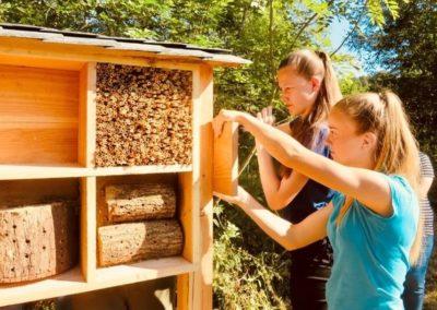 Die Teilnehmer*innen befestigen am Seitenrand des Bienenhotels ein Hinweisschild.