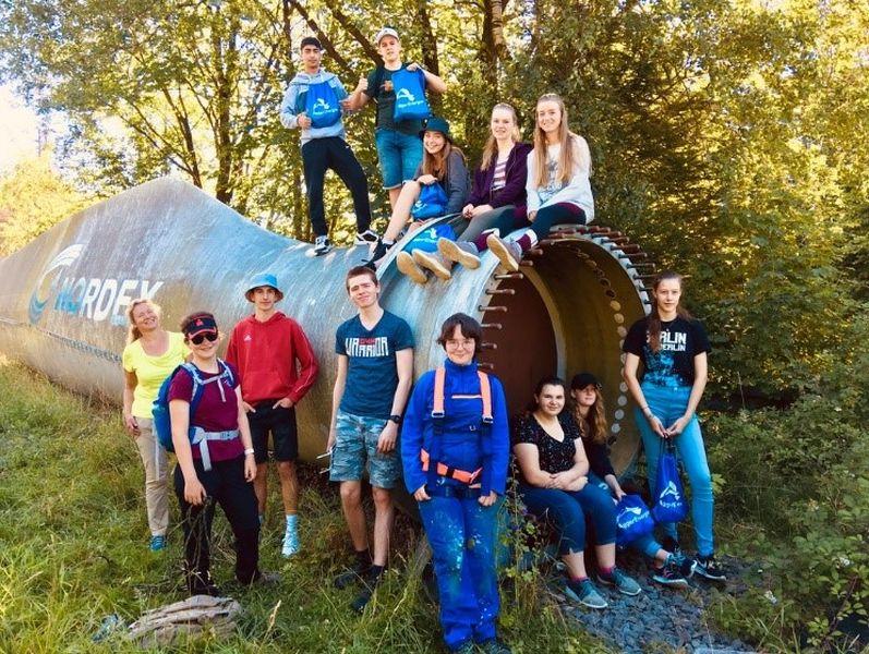 Jugendliche vor dem Rotorblatt im Wald.