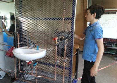 Ein Teilnehmer prüft die Verbindung der Wasserrohre an der Solaranlage.