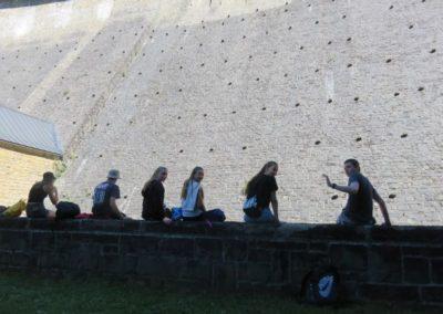 Jugendliche sitzen am Fuß der Aggertalsperre.