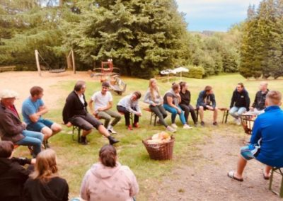 Jugendliche und Experte im Gespräch am Lagerfeuer.