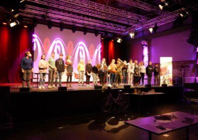 Geschafft: Die Teilnehmer*innen feiern ihr Event auf der Bühne.